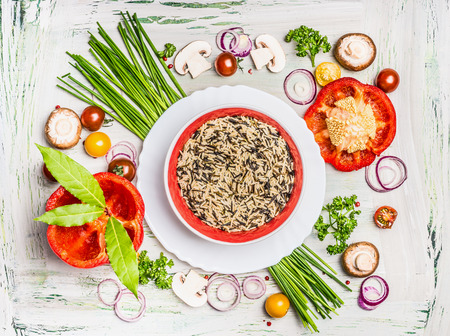 food concept: Wild rice dish and various vegetables and seasoning ingredients for tasty vegetarian cooking on light  rustic wooden background, top view composing. Healthy eating and diet food concept.
