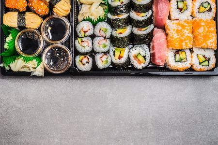 Variedad Sushi: rollos, nigiri, maki, rollos fuera y dentro de rollos en el fondo de piedra gris, vista desde arriba, borde horizontal. La comida japonesa y asiática.