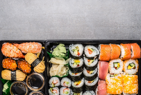 bento box: Various sushi menu in black transport box or bento box on gray  stone background, top view, border.  Japanese and Asian food.
