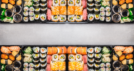 Varied Sushi sets assortment in bento boxes on gray stone background, top view, horizontal border or banner.  Japanese and Asian food.