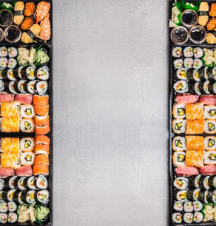 Varios conjuntos de sushi: rollos, nigiri, maki y uramaki en la bandeja de envasado negro sobre fondo gris piedra, vista desde arriba, marco. La comida japonesa y asiática.