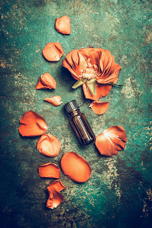 Rosen blüht mit dem Blumenblatt und ätherischem Öl auf dem rustikalen Weinlesehintergrund, kompostierendes der Draufsicht. Aromatherapie und Wellness-Konzept. Retro getönt