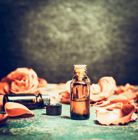 Roses essential oil in bottle on rustic vintage background, top view , place for text. Aromatherapy and cosmetic concept