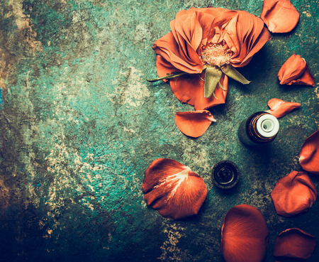 Roses flowers with petal and essential oil on rustic vintage background, top view , place for text. Aromatherapy and cosmetic concept