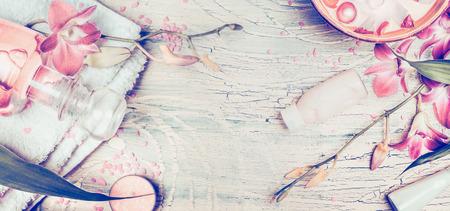 Wellness Hintergrund mit Orchideenblüten und Spa-Werkzeuge: Creme, Lotion, Handtuch und Wasserschüssel auf Shabby Chic Holz Hintergrund, Ansicht von oben, Banner. Pastell getönten Standard-Bild