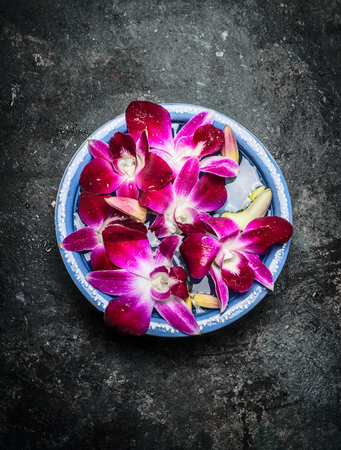 blue orchid: Blue bowl with water and pink orchid on dark rustic background, top view