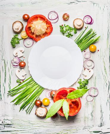 Verschiedene Gemüse und Gewürze Kochzutaten um leere Platte auf hellem rustikalen Holz Hintergrund, Ansicht von oben Komponieren. Gesunde Ernährung und Diät-Food-Konzept.