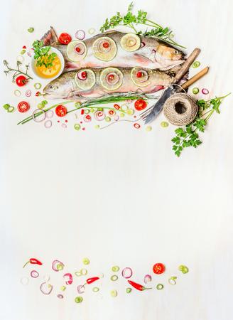 Visvoer achtergrond met rauwe hele vis, vers lekker koken ingrediënten en bestek op wit houten, bovenaanzicht, frame. Gezonde voeding of dieet concept. Visgerechten. Stockfoto