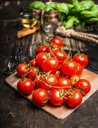bunch of: Cherry tomatoes bunch with water drops on dark rustic background