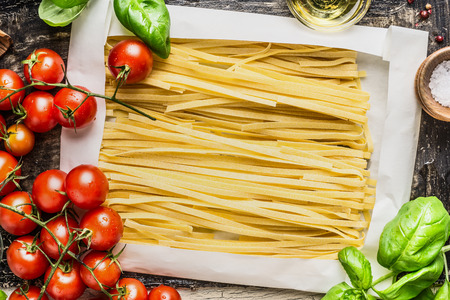 basil: Egg Noodles in wrapping paper and fresh cooking ingredients: basil and tomatoes, top view close up Stock Photo