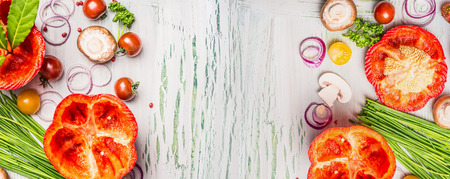 Alimentación de fondo con las verduras frescas picadas y condimentos para cocinar sobre fondo claro de madera rústica, vista desde arriba, bandera. La comida sana o concepto vegetariana. Foto de archivo