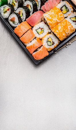 bento: Sushi set with tuna nigiri, inside and outside rolls in transport box on gray stone background, top view, place for text, border