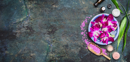 view on sea: Spa setting with water bowls , pink orchid flowers ,sea salt, cosmetic cream and essential oil on dark rustic background , top view, place for text, horizontal, banner. Wellness concept
