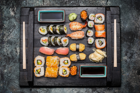 ouside: Sushi Set: maki, nigiri, ouside rolls served with soy sauce, pickled ginger and wasabi on dark wooden plate on rustic background, top view Stock Photo