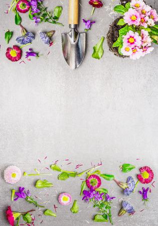 Blumen Anlage mit Erde und Gartenschaufel auf grauem Stein Hintergrund, Ansicht von oben, Platz für Text. Vertikale Grenze. Gartenarbeit Konzept Standard-Bild
