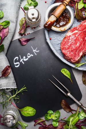marinate: Chalkboard cooking background with raw steak, meat fork,fresh seasoning and marinate, top view, place for text. Meat preparation for grill or BBQ