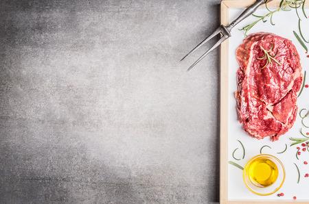 Ruwe Entrecote met vleesvork, olie en kruiden op steen achtergrond, bovenaanzicht, plaats voor tekst, grens Stockfoto