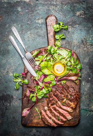 슬라이스 매체 드문 구운 쇠고기 바베큐 스테이크 소박한 커팅 보드에 신선한 그린 샐러드와 칼, 상위 뷰와 함께 제공합니다. 고기 음식