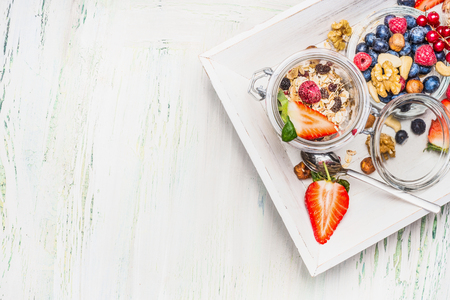 Healthy breakfast preparation: Muesli in jar with summer fresh berries, seeds and  nuts on light wooden background, top view,place for text