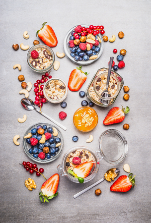 Muesli or granola in jars, fresh berries, seeds and  nuts  , top view. Healthy breakfast flat lay