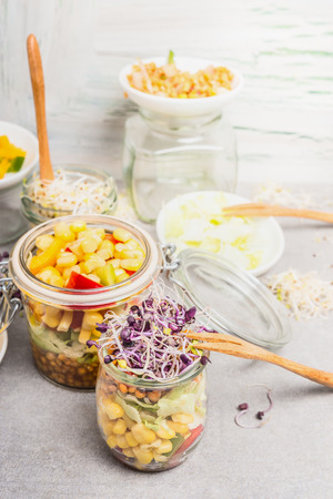 sprouts: Tasty vegetables salads in jars with corn and  sprouts on light rustic kitchen table, close up.  Healthy lifestyle or diet food concept