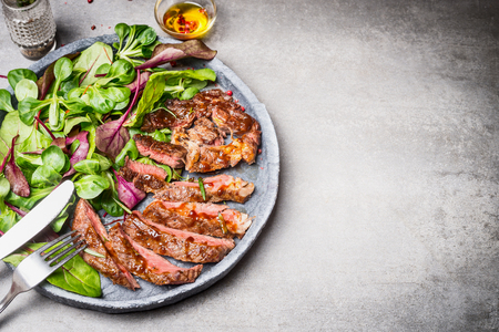 rare: Sliced grilled beef steak with green leaves salad on rustic plate with cutlery. Medium rare barbecue steak and healthy salad on gray stone background, top view, place for text