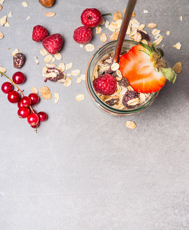 oats: Muesli with oat flakes, dried fruits, nuts and fresh berries. Muesli in glass jar, top view.  Healthy food and Clean Eating concept Stock Photo