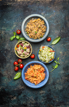 Variety of delicious salads dish on dark rustic background, top view. Healthy food and Clean Eating concept