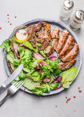 plato de ensalada: Sliced medium rare grilled barbecue steak and green salad on stone plate with cutlery, top view