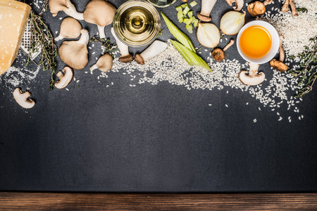 wild rice: Mushrooms risotto ingredients on black chalkboard background, top view. Italian food
