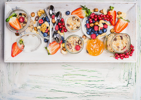 light breakfast: Healthy breakfast with muesli and summer berries and nuts. Fresh granola, muesli and berries in glass jars on light shabby chic wooden background, top view, place for text Stock Photo