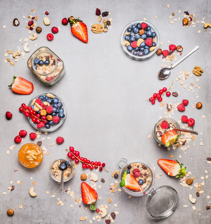 Healthy Breakfast round frame. Various fresh berries, muesli and nuts on gray background. Muesli or granola in jars. Healthy food and Clean Eating concept