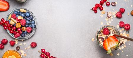Muesli, noten en bessen. Ontbijt voorbereiding. Muesli met verse bessen in pot op stenen achtergrond, bovenaanzicht, banner. Gezond voedsel en schoon eten concept