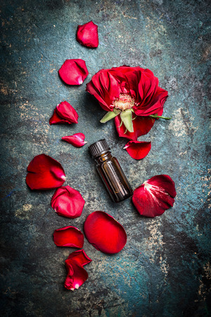 dark red: Red roses and bottle of essential oil on dark rustic background, top view