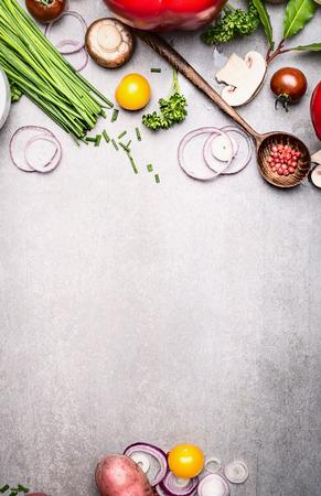Gesundes Kochen mit Frischgemüse und Gewürzbestandteilen auf rustikalem Steinhintergrund, Draufsicht, Platz für Text, Rahmen. Gesundes Lebensstil- und Diätlebensmittelkonzept.