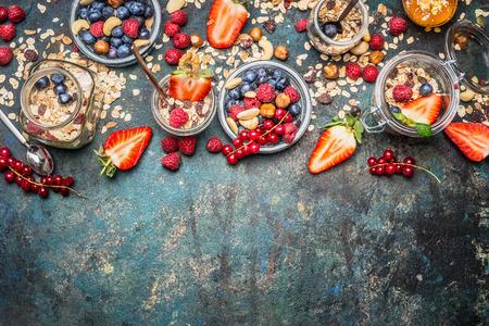 Muesli met verse bessen, noten en zaden. Evenwichtig ontbijt ingrediënten op rustieke achtergrond. Muesliontbijt in glazen potten, bovenaanzicht, grens. Gezonde levensstijl en voeding eten concept.
