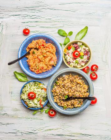 barra de cereal: Sanos cuencos de ensalada vegetarianas en el fondo rústico, vista desde arriba. plato de ensaladas variadas
