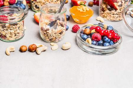 clean food: Muesli mix with nuts and berries in glass jars on light background, close up. Healthy lifestyle and Clean food concept.