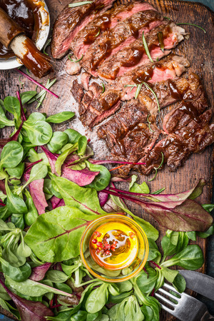 close up view: Sliced grilled steak served with green salad, Barbecue sauce and cutlery , close up, top view