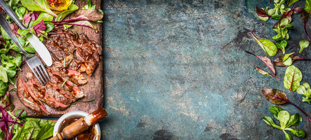 fried food: Perfectly fried or grilled steak. Sliced Beef seak , served with green salad leaves and Barbecue sauce on wooden cutting board and rustic background, top view, banner