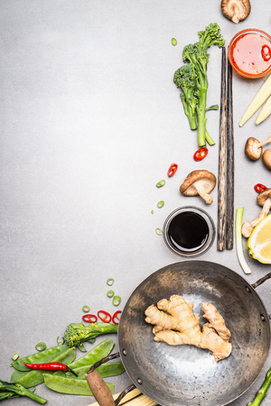 Stir fry ingredients with wok and chopsticks. Asian cuisine cooking ingredients on gray stone background, top view.