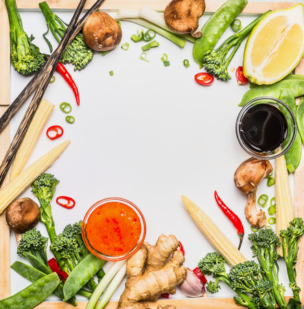 Traditional asian vegetables cooking  ingredients with soy sauce and chopsticks. Chinese or Thai food on white chalkboard background, top view, frame