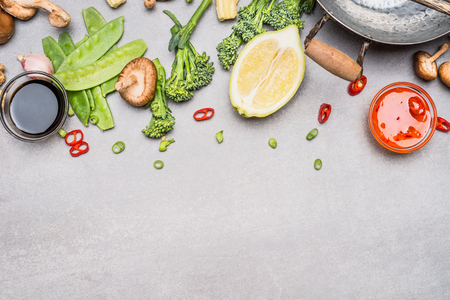 Chinese or Thai cuisine vegetables and spices cooking ingredients on gray stone background, top view, border