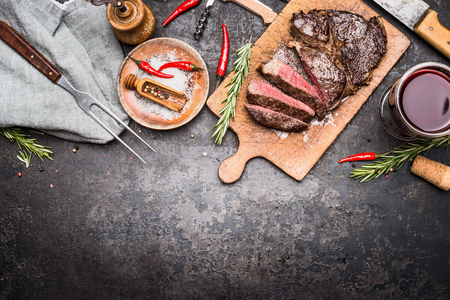 Roasted sliced grill steak on wooden cutting board with wine, seasoning and meat fork on dark vintage metal background, top view, border