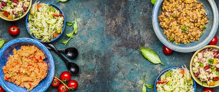 Healthy different salad bowls on dark vintage background. Country salads in rustic bowls. Salad bar, top view, banner. Healthy food or vegetarian eating concept Standard-Bild