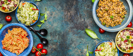 Healthy different salad bowls on dark vintage background. Country salads in rustic bowls. Salad bar, top view, banner. Healthy food or vegetarian eating concept Archivio Fotografico