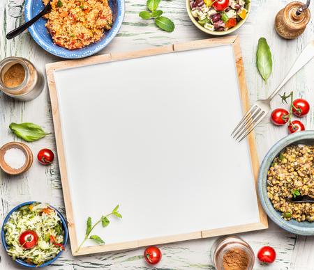 Verschillende gezonde vegetarische salades bowlen rond blanco wit bord, bovenaanzicht. Salade bar. Voedselachtergrond voor menu, recepten of uw tekst