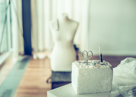 made to measure: Sewing pins, scissors and pin cushion over modern workshop or studio with dummy , toned