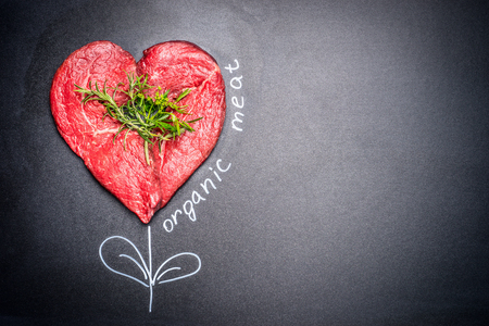 eater: Heart shape raw meat with herbs with painted  Organic meat inscription around . Dark chalkboard background. Healthy lifestyle or organic food concept. For Meat lovers and eater