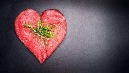 어두운 칠판 배경에 허브와 함께 심장 모양 원시 고기. 건강 한 라이프 스타일 또는 유기농 식품 개념입니다. 고기 애호가 및 먹는 사람들을위한